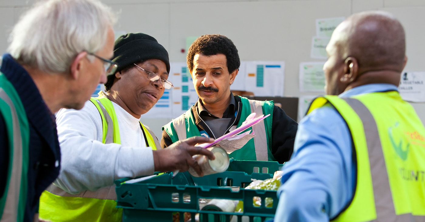 Four FareShare workers organising a crate of food to be donated to the FareShare Charity
